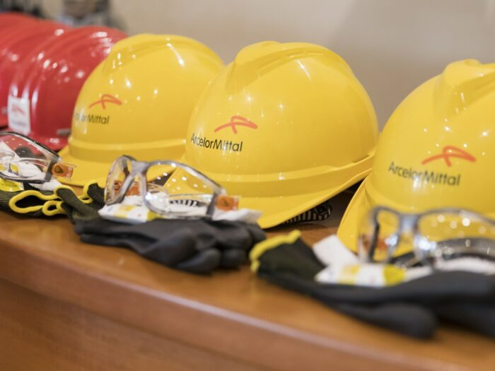 A row of yellow construction hats with the ArcelorMittal logo