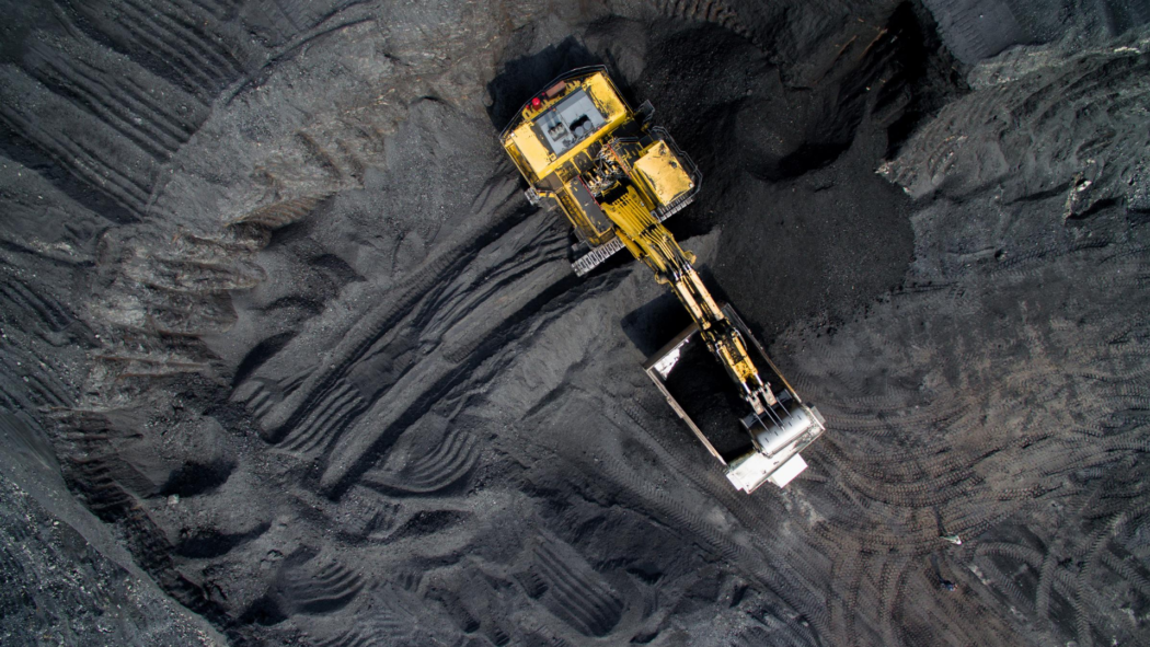An aerial view of a coal mine with a yellow machine at the centre