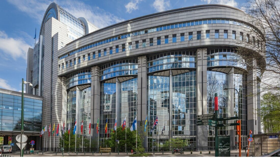 The exterior of the European Parliament building in Brussels, with a row of flags in the front
